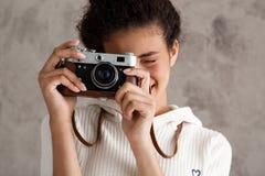 Sorridere femminile africano della fotografia, prendente le immagini sopra fondo beige Fotografia Stock