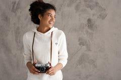 Sorridere femminile africano della fotografia, tenente macchina fotografica sopra fondo beige Fotografie Stock Libere da Diritti