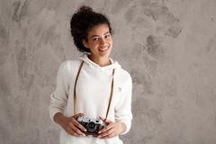 Sorridere femminile africano della fotografia, tenente macchina fotografica sopra fondo beige Fotografia Stock