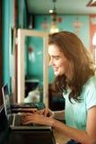 Sorridere femminile dell'istituto universitario al caffè e lavorare al computer portatile Fotografie Stock