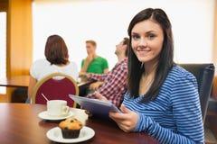 Sorridere femminile mangiando prima colazione mentre per mezzo del PC della compressa alla caffetteria Fotografia Stock Libera da Diritti