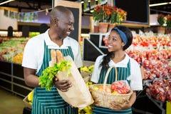 Sorridere fornisce il canestro della tenuta ed il sacco di carta di personale delle verdure Immagini Stock Libere da Diritti