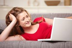Sorridere teenager con il computer portatile sul sofà nel paese Fotografia Stock