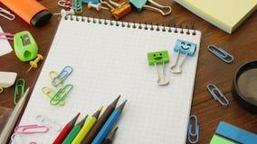 Sorriem os grampos azuis e verdes da pasta no caderno com lápis e os clipes de papel multi-coloridos filme