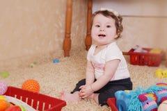 Sorrindo dez meses de bebê que joga com brinquedos Imagens de Stock