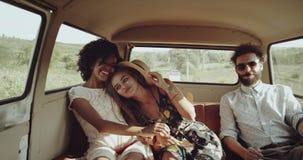 Sorrindo duas meninas retros perfeitas africanas e o louro, abraçando-se ao lado deles é um homem novo tem uma cara feliz vídeos de arquivo
