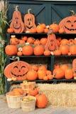 Sorrindo Jack-O-lanternas e várias abóboras no shelving verde Fotografia de Stock