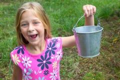 Sorrindo a menina que guarda um balde vazio fotografia de stock royalty free