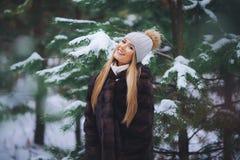 Sorrindo, moça feliz que anda na floresta do inverno Fotografia de Stock