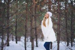 Sorrindo, moça feliz que anda na floresta do inverno Fotos de Stock Royalty Free