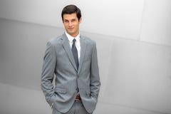 Sorrindo o homem de negócios em uma expressão nova e positiva na moda do terno no líder incorporado moderno do escritório Foto de Stock