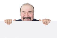 Sorrindo o homem de negócios que guarda um sinal branco vazio Fotografia de Stock Royalty Free