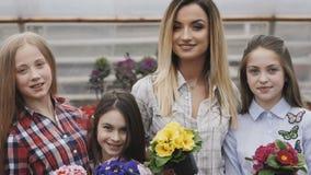 Sorrindo quatro meninas com os vasos de flores nas mãos que olham a câmera vídeos de arquivo