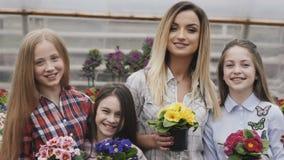 Sorrindo quatro meninas com os vasos de flores nas mãos que olham a câmera video estoque