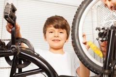 Sorrindo seis anos de menino idoso que repara sua bicicleta Imagens de Stock