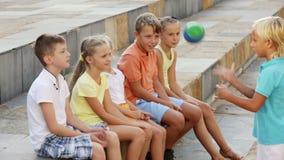 Sorrir caçoa na idade escolar que tem o divertimento que joga a bola junto