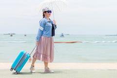 Sorrir mulheres está guardando o guarda-chuva e puxar a bagagem azul moderna do rolamento duramente Imagem de Stock Royalty Free