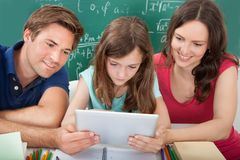Sorrir parents a ajuda da filha em usar a tabuleta digital Fotografia de Stock