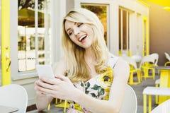 Sorrisi biondi della donna al suo Smart Phone mentre sedendosi ad un Cafre all'aperto fotografie stock libere da diritti