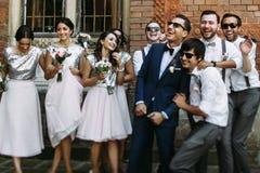 Sorrisi dello sposo con le damigelle d'onore ed i groomsmen Fotografia Stock