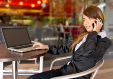 Sorrisi di giovane donna di affari asiatica sul telefono Fotografia Stock Libera da Diritti