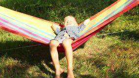 Sorrisi di Little Boy che godono dei raggi del sole in amaca stock footage
