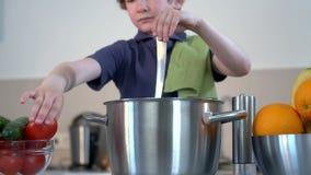 Sorrisi divertenti piccoli del ragazzo e minestra del cuoco nella cucina video d archivio