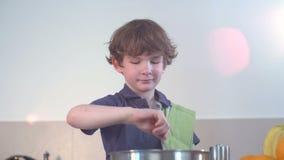 Sorrisi divertenti piccoli del ragazzo e minestra del cuoco nella cucina stock footage