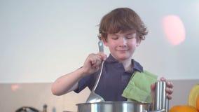 Sorrisi divertenti piccoli del ragazzo e minestra del cuoco nella cucina archivi video