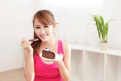 Sorrisi felici della donna che mangiano il dolce di cioccolato Immagine Stock