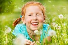 Sorrisi piacevoli della bambina che mettono su un'erba Immagini Stock