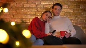 Sorriso abraçando os pares caucasianos que sentam-se no sofá e escolha de filmes na tevê com o copo da bebida na casa confortável vídeos de arquivo