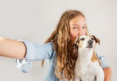 Sorriso adolescente com o cão que faz a foto do selfie no smartphone sobre a menina bonito do fundo branco foto de stock royalty free