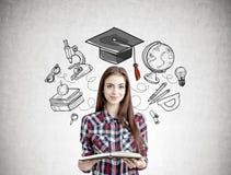 Sorriso adolescente com um livro, ícones da educação Fotos de Stock
