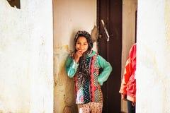 Sorriso amigável bonito da criança da menina em Fes antigo Medina com o vestido tradicional de musselina, Fes, Marrocos imagem de stock