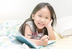 Sorriso asiático bonito e escrita da menina ao diário na cama Fotos de Stock Royalty Free