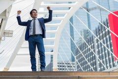 Sorriso asiático do homem de negócios e levantar acima duas mãos para alegre e comemoradas seu bem sucedido na carreira e na miss fotografia de stock royalty free