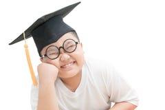 Sorriso asiatico del laureato del bambino della scuola con il cappuccio di graduazione isolato Fotografia Stock Libera da Diritti