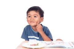 Sorriso asiatico del ragazzino di Childe e pensare mentre facendo compito immagini stock libere da diritti