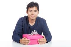 Sorriso asiatico dell'uomo con un contenitore di regalo rosa Fotografie Stock Libere da Diritti