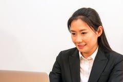Sorriso asiatico della donna durante i dati di battitura a macchina Immagine Stock