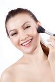 Sorriso asiatico della donna mentre si applicano componga Immagine Stock