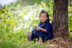 Sorriso asiatico di seduta della ragazza sull'erba nel parco fotografia stock
