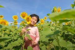 Sorriso asiatico sveglio della ragazza con il fiore del girasole fotografia stock libera da diritti