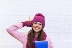 Sorriso attraente di Girl Happy Emotional dello studente in matita rosa della cartella della tenuta del cappello Fotografia Stock Libera da Diritti