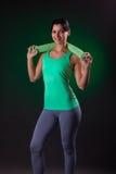 Sorriso bonito atlético, posição da mulher da aptidão, levantando com uma toalha em um fundo cinzento com um luminoso verde Imagens de Stock Royalty Free