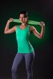 Sorriso bonito atlético, posição da mulher da aptidão, levantando com uma toalha em um fundo cinzento com um luminoso verde Imagem de Stock
