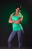 Sorriso bonito atlético, posição da mulher da aptidão, levantando com uma toalha em um fundo cinzento com um luminoso verde Fotos de Stock Royalty Free