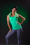 Sorriso bonito atlético, posição da mulher da aptidão, levantando com uma toalha em um fundo cinzento com um luminoso verde Imagens de Stock