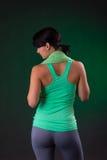 Sorriso bonito atlético, posição da mulher da aptidão, levantando com uma toalha em um fundo cinzento com um luminoso verde Fotografia de Stock Royalty Free